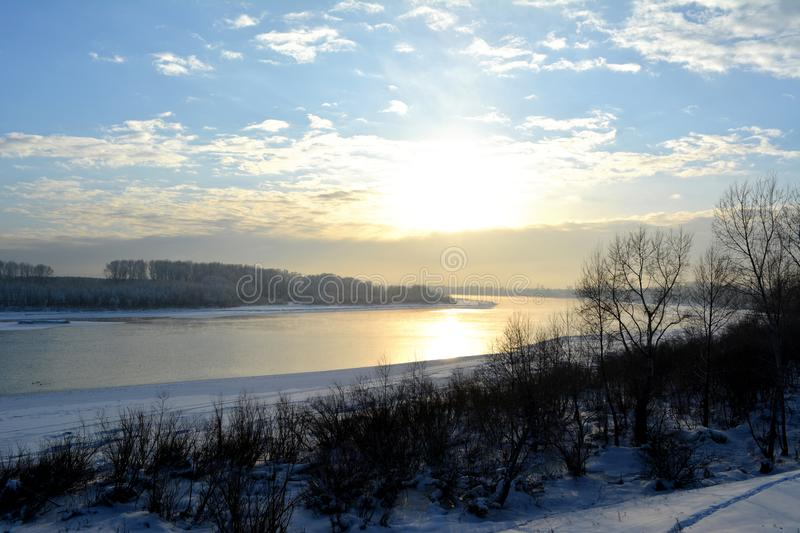 Winter scene with non frozen river. Wonderland view of beginning of sunset. royalty free stock photography