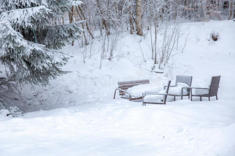 Winter scene in a rest zone near a forest. Benches and snowmen, forest road. Winter scene in snowy park in a rest zone near a forest. Benches and snowmen, forest royalty free stock images