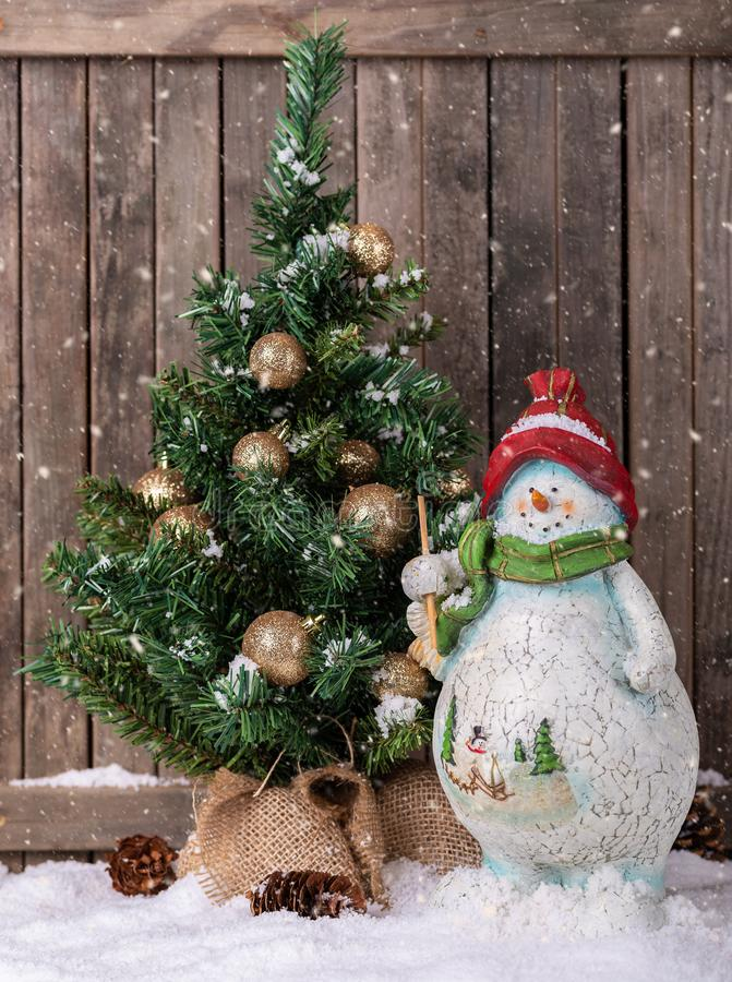 Winter Scene of Snowman and Christmas Tree royalty free stock photos