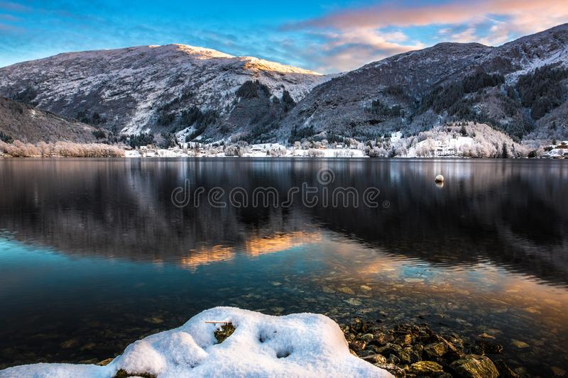 Winter Scene with Snowy Mountains, Colorful Clouds and Lake Reflection at Dusk royalty free stock photography