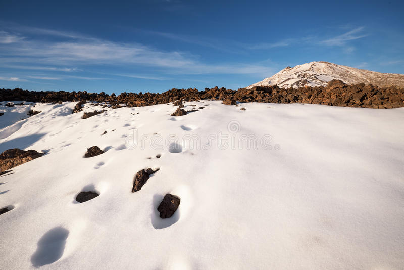 Winter scene of Teide national park at sunset with volcanic rocks and snow, in Tenerife, Canary islands, Spain. stock images