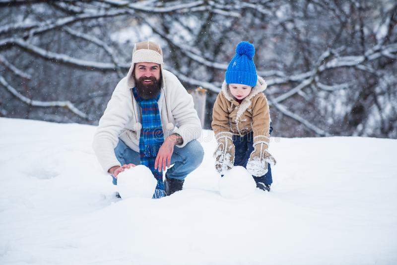 Winter scene on white snow background. Family holiday and togetherness. Happy child playing with snowball against white royalty free stock images