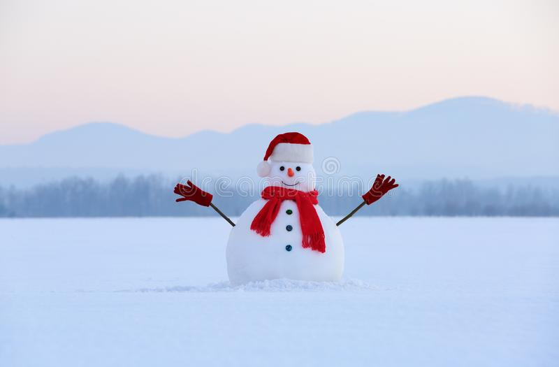 Snowman in red hat and scarf. Christmas scenery. High mountains at the background. Ground covered by snow. Winter scenery. Christmas snowman wearing red hat stock photos