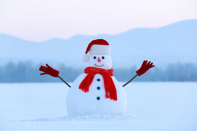 Winter scenery. Christmas snowman wearing red hat, scarf and gloves. High mountains. Snowman in red hat and scarf. Christmas scenery. High mountains at the royalty free stock images