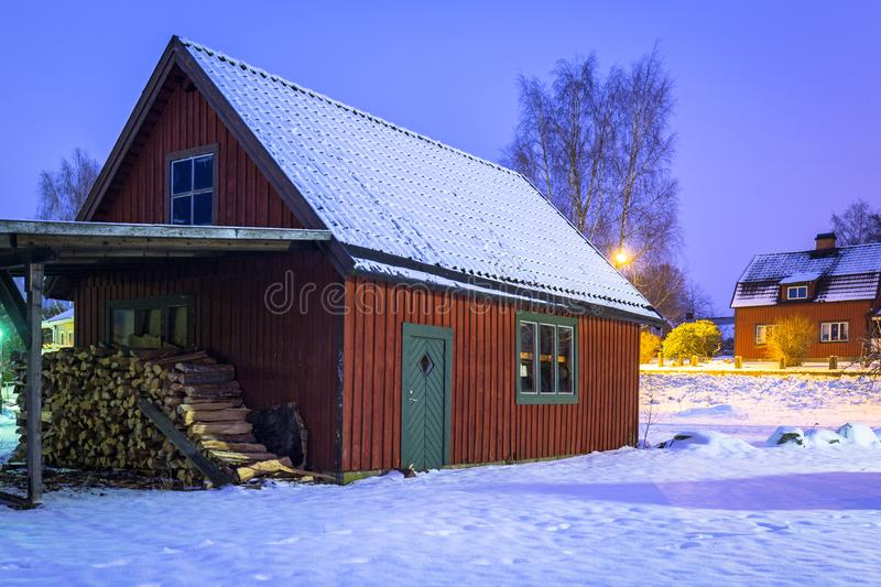 Winter scenery with cottage wooden house in Sweden at night. Road kyrkhult snow red nature lapland street beautiful landscape lamp northern white travel royalty free stock images