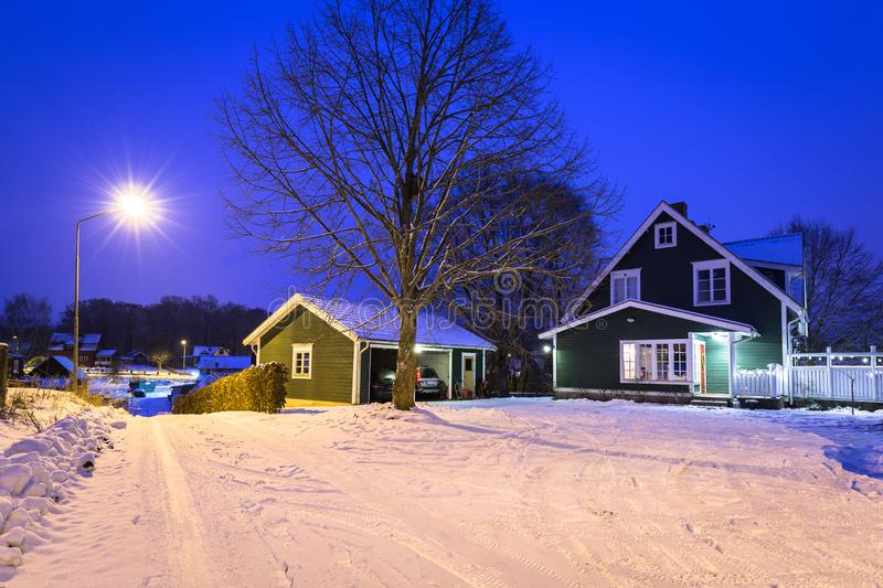 Winter scenery with cottage wooden house in Sweden at night. Road kyrkhult snow red nature lapland street beautiful landscape lamp northern white travel stock image