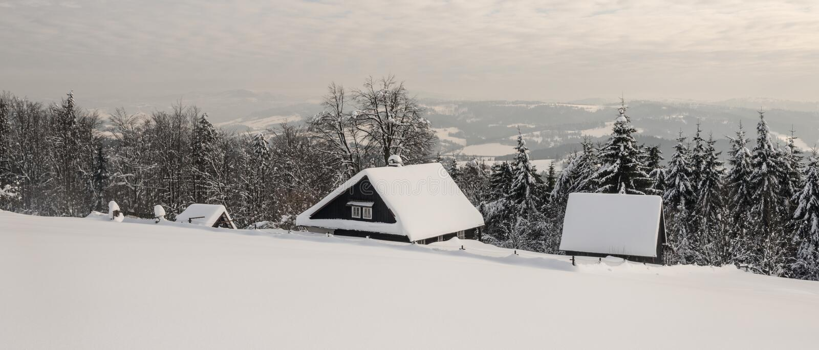 Winter scenery with few houses surronded by trees and hilly landscape on the background. Above Bukovec village in easternmost part of Czech republic near royalty free stock photography