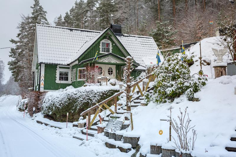 Winter scenery with green wooden house in Sweden royalty free stock photography