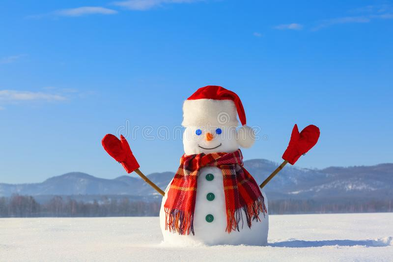 Winter scenery. Happy snowman in hat, red gloves and scarf on the background of mountains , blue sky. Field covered with snow. stock image