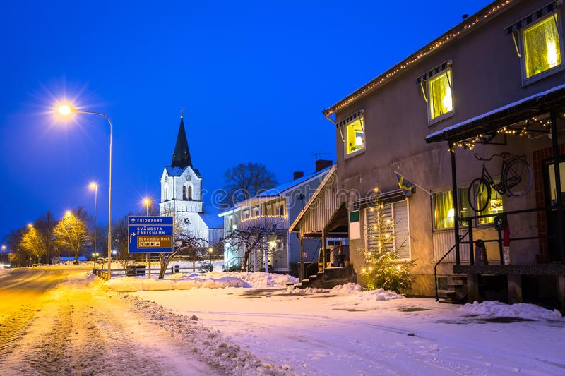Winter scenery of Kyrkhult village in Sweden at night. Road snow house red nature lapland street beautiful landscape lamp northern white travel blekinge cottage royalty free stock images