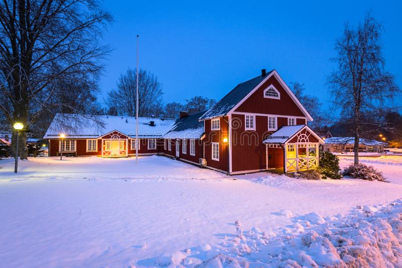 Winter scenery with red wooden house in Sweden at night. Road kyrkhult snow nature lapland street beautiful landscape lamp northern white travel blekinge royalty free stock photos