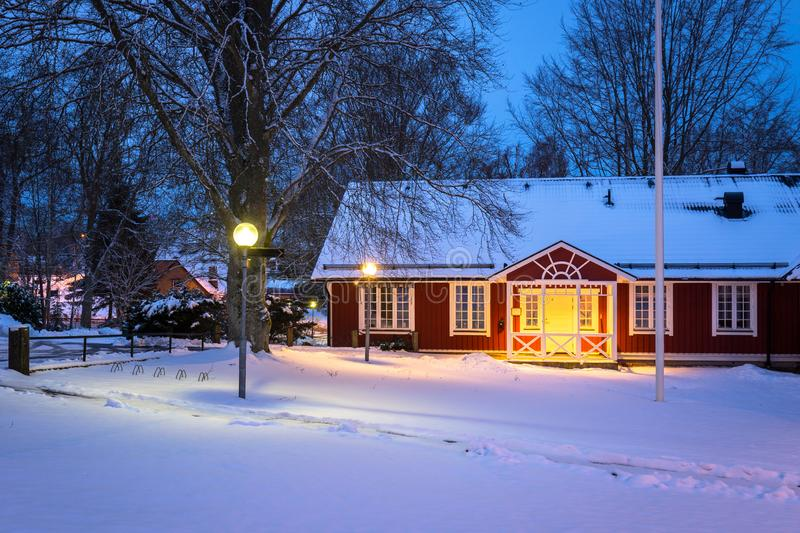 Winter scenery with red wooden house in Sweden at night. Road kyrkhult snow nature lapland street beautiful landscape lamp northern white travel blekinge royalty free stock image