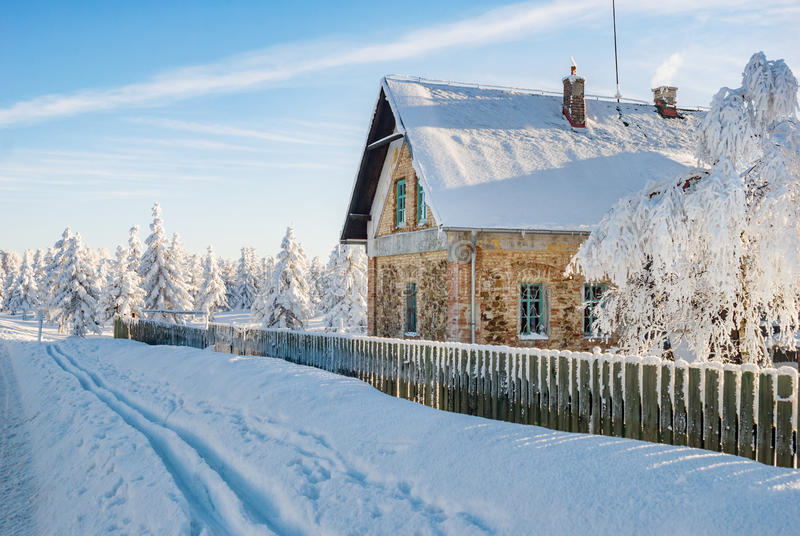 Winter scenery with small house. Winter scenery with small public house chalet, ski trail and snow covered trees with morning dawn light stock image