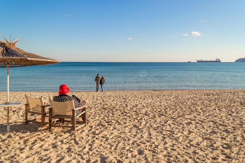 Winter sea beach and calm sea on a sunny day. A lonely elderly woman sits in a deck chair facing the sea. A loving couple stands stock photos