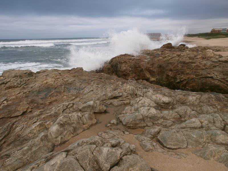 Winter sea scene with waves splash on rocks royalty free stock image