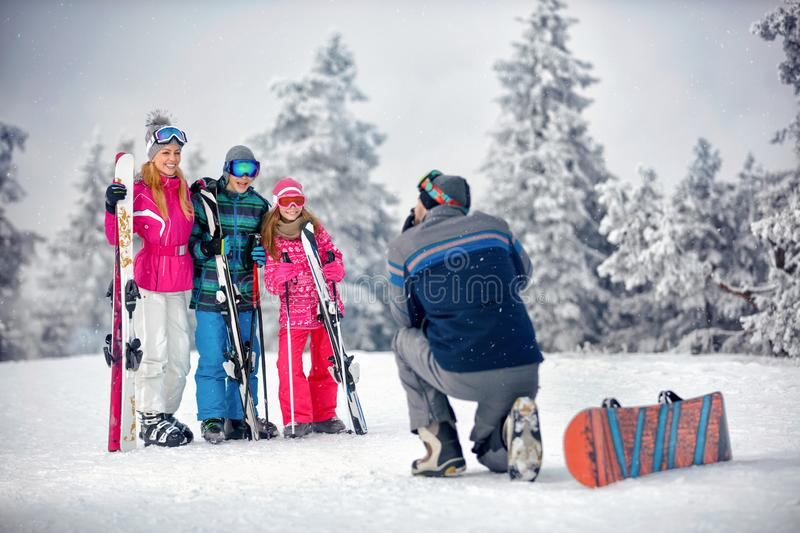Winter season - father take photographing family on vacation in. Winter season - father take photographing happy family on vacation in snow mountains stock photos