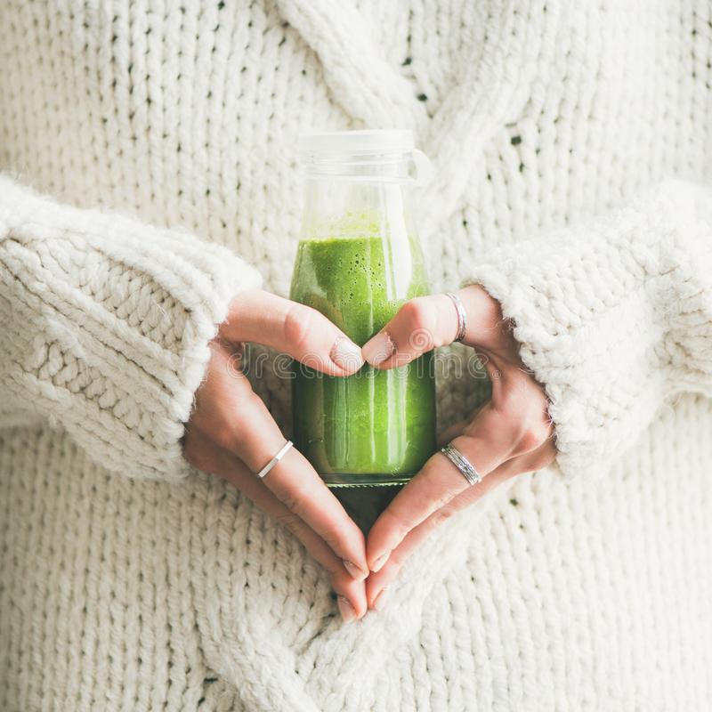 Winter seasonal smoothie drink detox in woman`s hands, square crop. Winter seasonal smoothie drink detox. Female in sweater holding bottle of green smoothie or stock photos