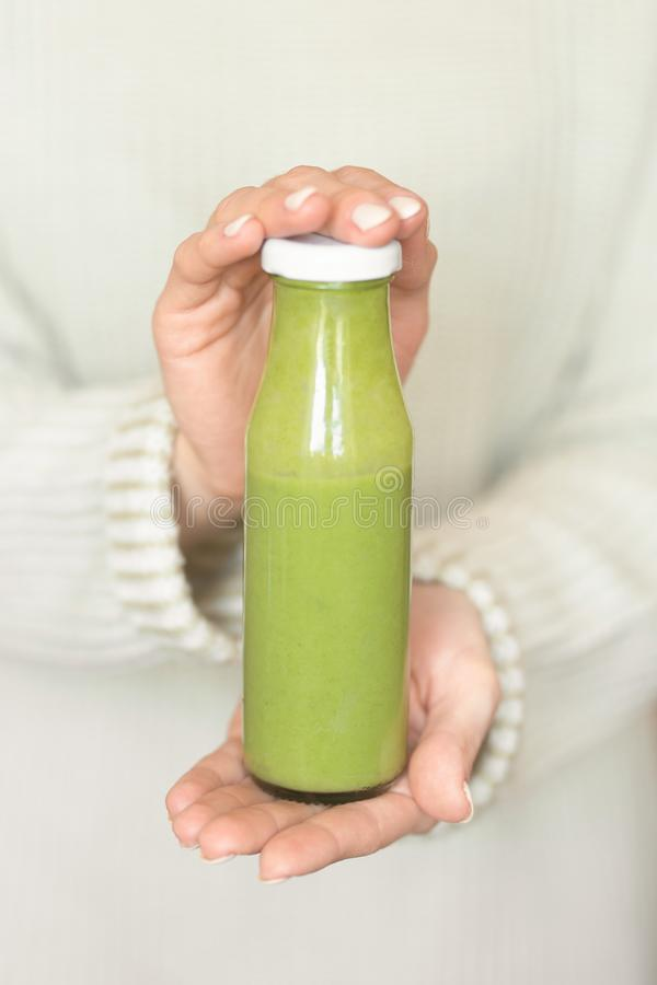 Winter seasonal smoothie drink detox. Girl in a woolen sweater, holding a bottle of green smoothie or juice. Diet, Clean Food,. Weight Loss, Healthy Diet royalty free stock image