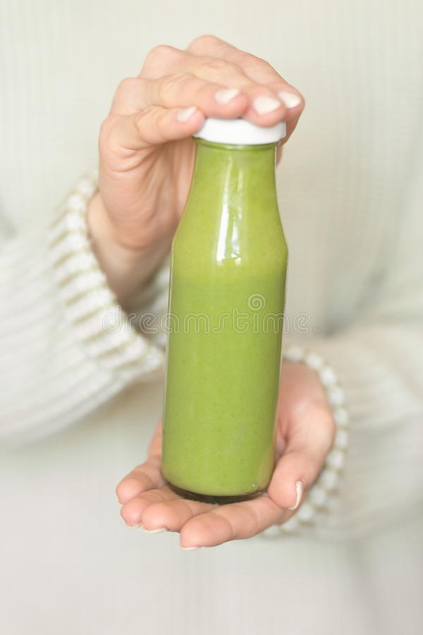 Winter seasonal smoothie drink detox. Girl in a woolen sweater, holding a bottle of green smoothie or juice. Diet, Clean Food,. Weight Loss, Healthy Diet stock photography