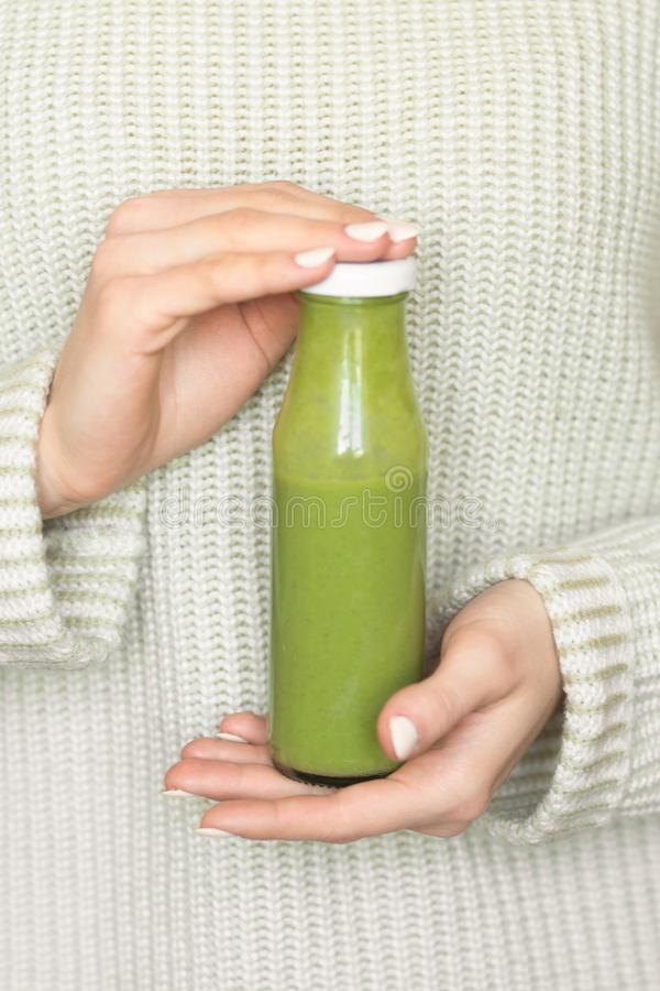 Winter seasonal smoothie drink detox. Girl in a woolen sweater, holding a bottle of green smoothie or juice. Diet, Clean Food,. Weight Loss, Healthy Diet royalty free stock photography