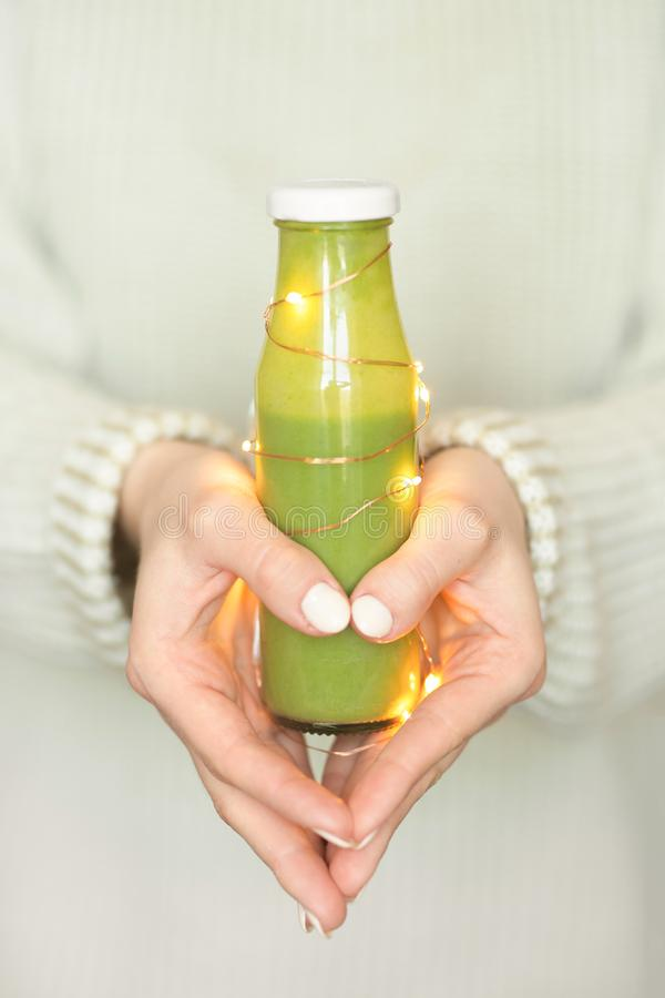 Winter seasonal smoothie drink detox. Girl in a woolen sweater, holding a bottle of green smoothies, making a heart shape with his. Own hands. Diet, Clean Food stock photos