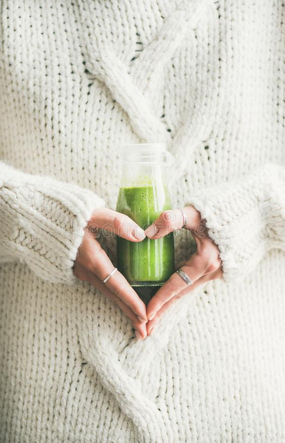 Winter seasonal smoothie drink detox in woman`s hands. Winter seasonal smoothie drink detox. Female in warm sweater holding bottle of green smoothie or juice royalty free stock images