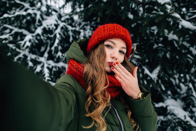Girl sends kiss in camera in winter cold day. Winter selfie. Young girl in red winter hat sends kiss in camera in winter cold day stock photo