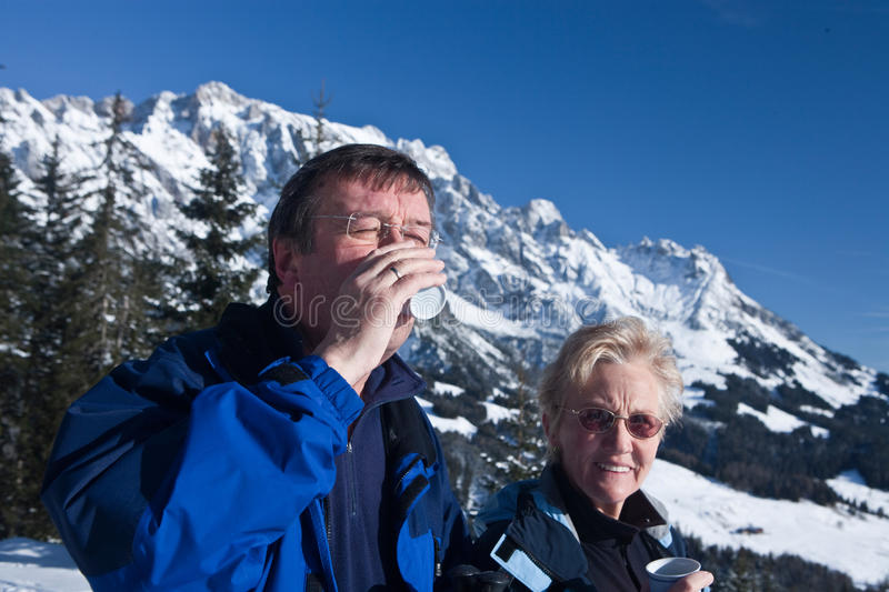 Winter-seniors. A senior couple in a winter setting in the alpine mountains. Active and happy seniors.They are having a cup of tea royalty free stock photo