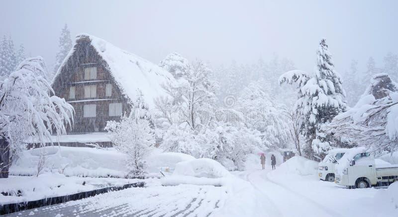 Winter at Shirakawa-go village in Gifu, Japan. People walking on the road in snow storm in Gifu, Japan royalty free stock photography