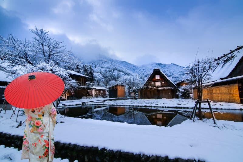 Winter Shirakawago con Snowfall Gifu Chubu Giappone e Una ragazza che indossa uno yukata con un ombrello rosso immagine stock libera da diritti