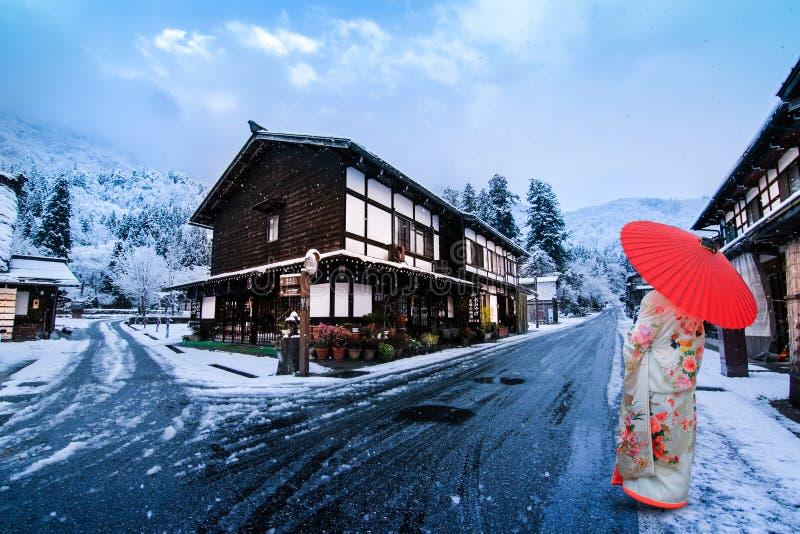 Winter Shirakawago con Snowfall Gifu Chubu Giappone e Una ragazza che indossa uno yukata con un ombrello rosso fotografia stock libera da diritti