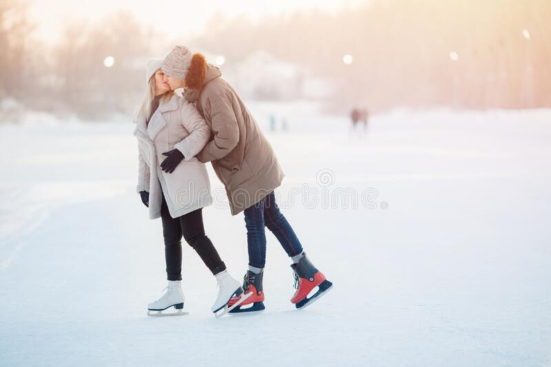 Winter skates, loving couple holding hands and rolling on rink. Concept training stock images