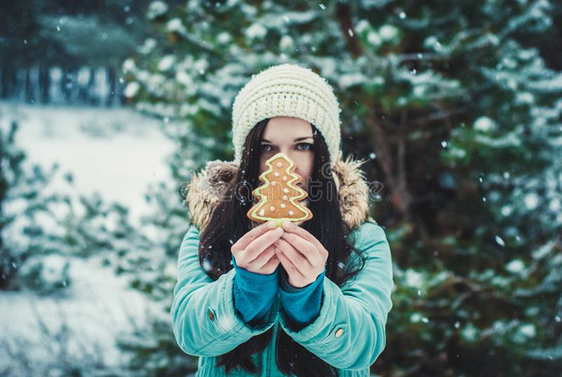 Winter smiling girl eating oatmeal and Gingerbread Cookie outdoor. Lifestyle photo stock image