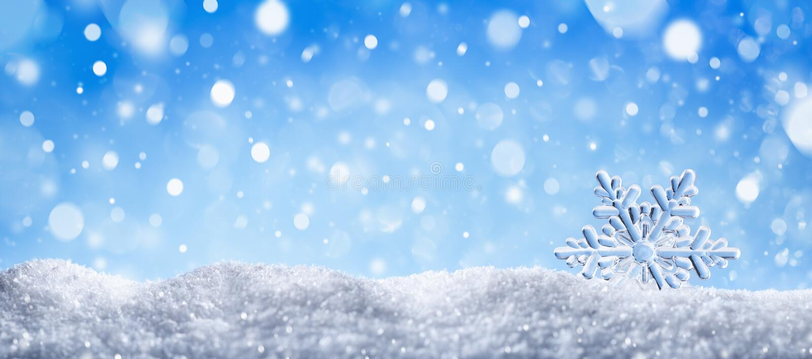 Winter snow background with decorative snowflake against blue sky. Banner format. Beautiful wintertime holiday scene. Winter snow background with decorative royalty free stock photo