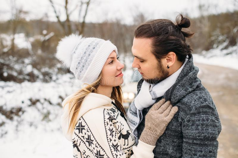 Winter snow couple love story. Beautiful girl in cozy hat and handsome bearded man hugs each other. pullover with stock photos