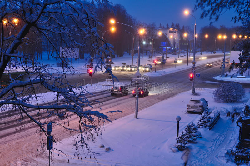 Winter snow disaster in a city. snowstorm on a road, cars in snow. Top view to avenue covered with snow in early morning or evenin stock photography