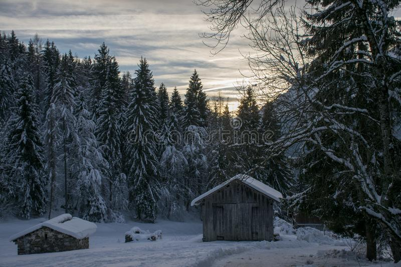 Winter barns at sunset. Winter, snow, dwelling, landscape, cold, trees, forest, nature, cabin, mountain, bungalow, building, village, white, barn, sky, farm royalty free stock photos