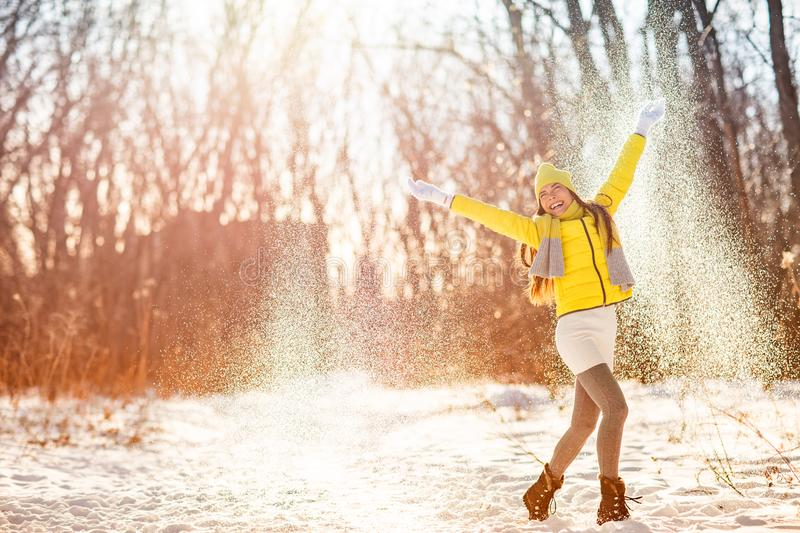 Winter snow fun woman playing throwing snow celebrating cold weather. Girl in yellow outerwear gloves, boots, hat, scarf, coat, royalty free stock photos