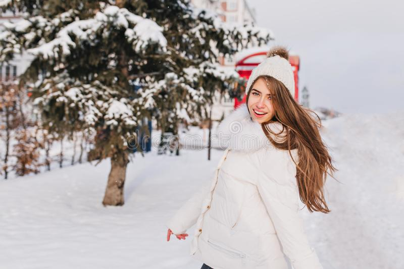 Winter snow happiness of joyful attractive girl with long brunette hair walking on street. Happy sunny winter morning of royalty free stock photography