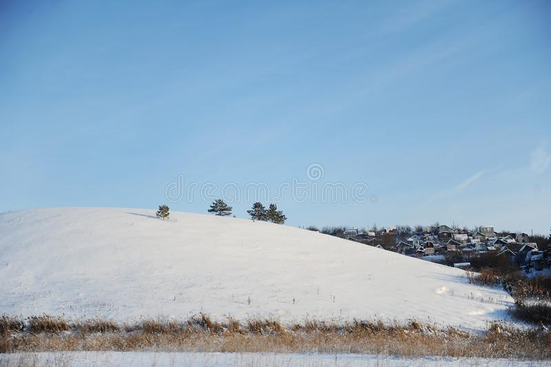 Winter snow landscape. The trees on the hill and the village behind the mountain. Bright blue sky royalty free stock images