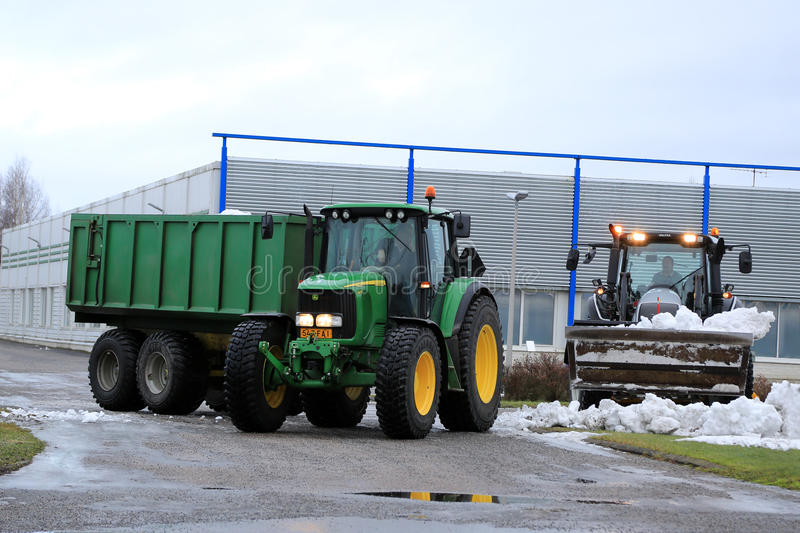 Winter Snow Removal with John Deere and Valtra Tractors. SALO, FINLAND - JANUARY 18, 2015: Unidentified workmen removing snow with Valtra and John Deere tractos stock photos