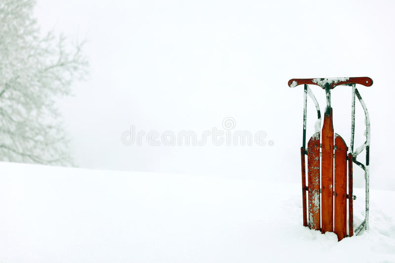 A winter snow scene background with a red vintage upright sled. A horizontal presentation of mountain snow with a red antique sled on the right and an empty royalty free stock image