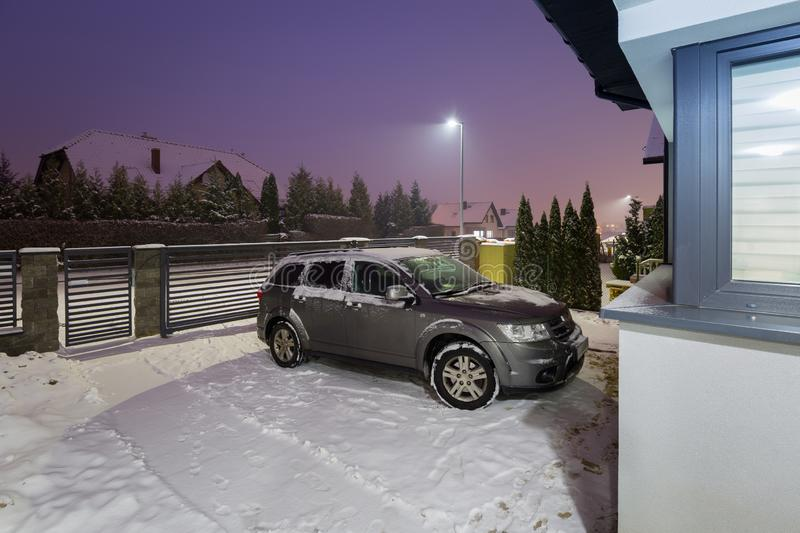 Winter snowfall at the parking area by night. New fence stone stonework house outdoor nobody architecture dusk twilight dark home gray concrete wall car suv stock image