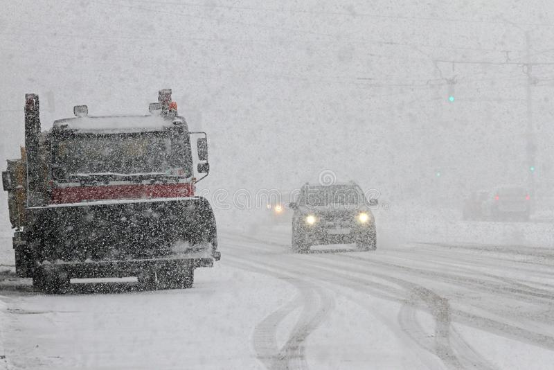 Winter. Snowplow cleans the road in the city during a huge snowstorm, Snow clean machine on boulevard with cars in big snowfall stock photos