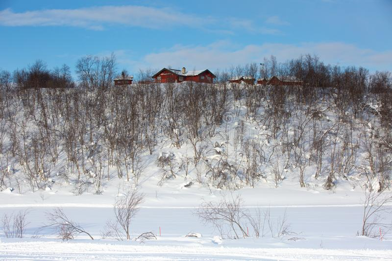 Winter snowy sunny landscape. Wooden house on the high bank of a river or lake. Norway stock photography