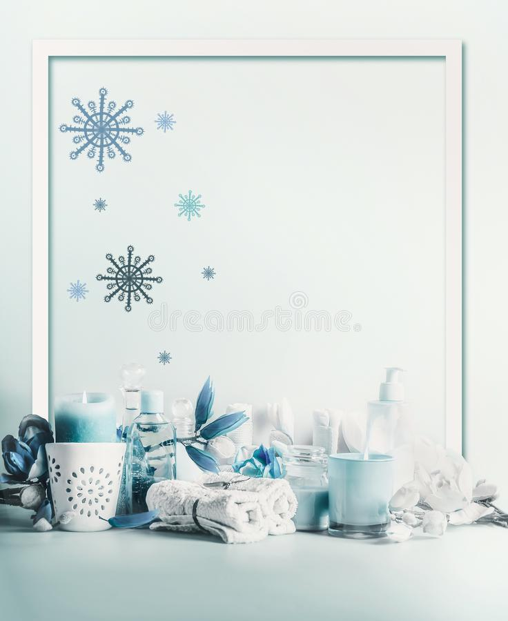 Winter spa and wellness concept. Winter skin and body care. Cosmetic products. Holiday spa day. Frame. Blue composition of candles. Towels, and flowers. Winter royalty free stock photo