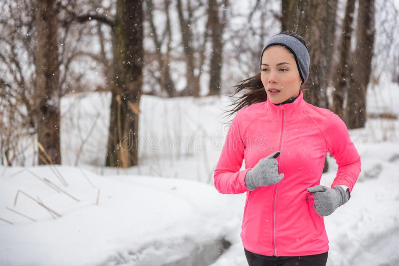 Winter sport fitness girl running in snow wearing wind jacket, gloves, headband and smartwatch. Asian woman healthy and active royalty free stock photos