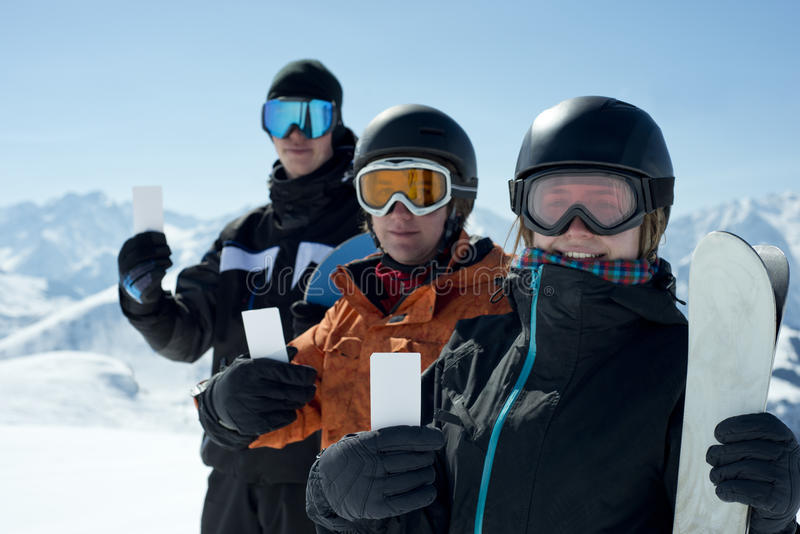 Winter sport group admission pass. Group of winter sport people showing ski lift pass looking. Concept to illustrate ski admission fee royalty free stock photo