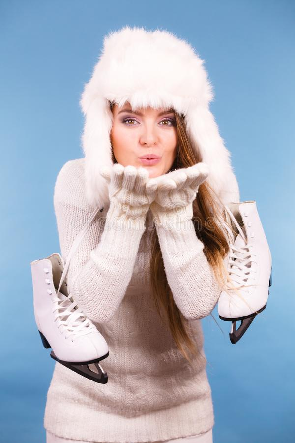 Woman wearing fur cap holding ice skates. Winter, sport, people concept. Attractive lady with ice skates. Young woman wearing fur cap sending air kiss royalty free stock photos