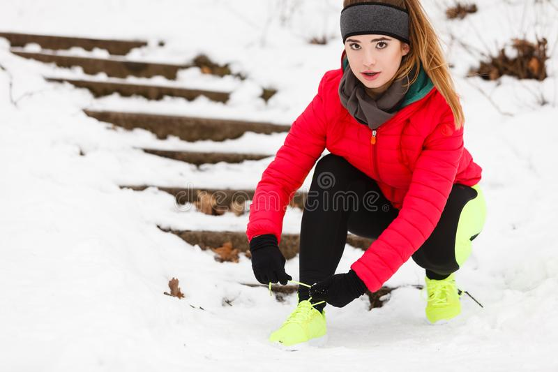 Woman tying sport shoes during winter royalty free stock photography